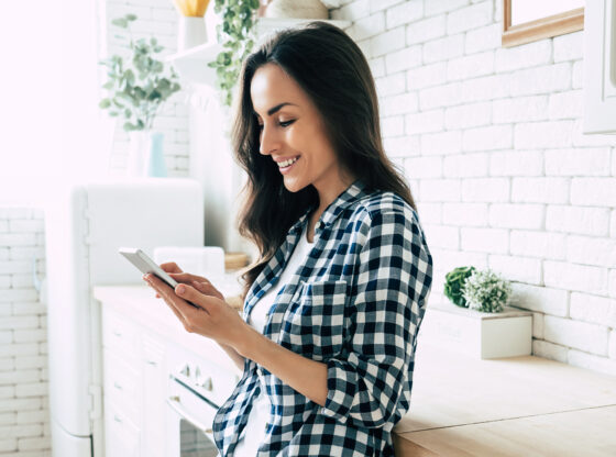 woman smiling while looking at smartphone